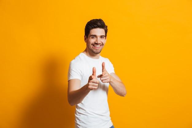 Zadowolony facet w białej koszulce śmiejąc się i wskazując palcem na aparat