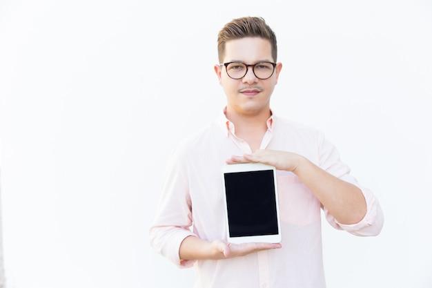 Zadowolony facet w okularach prezentacji pusty ekran tabletu