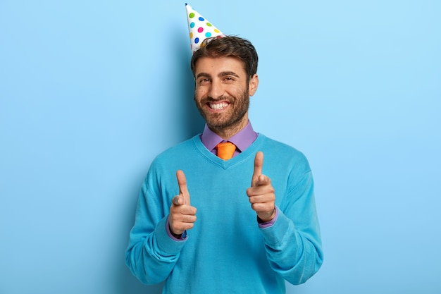 Zadowolony facet z urodzinową czapką pozuje w niebieskim swetrze