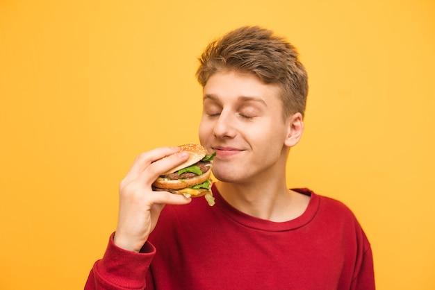 Zadowolony facet z zamkniętymi oczami iz burgerem w rękach na żółtym.