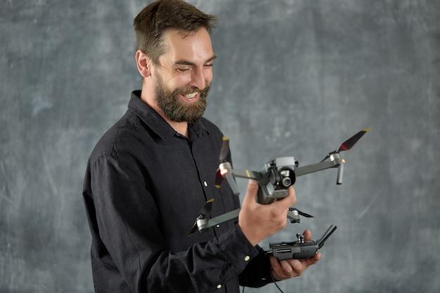 Zadowolony filmowiec trzyma w dłoni nowy quadkopter