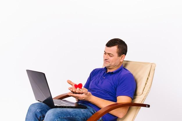 Zadowolony głuchy starszy mężczyzna trzyma aparat słuchowy i czerwone serce przed kamerą w laptopie