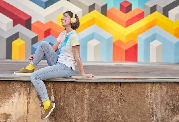 Zadowolony hipster kobieta uśmiechając się i ciesząc się dobrą muzyką