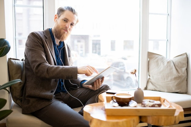 Zadowolony hipster mężczyzna pracujący w kawiarni