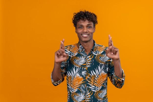 Zadowolony i pozytywnie nastawiony młody przystojny ciemnoskóry mężczyzna z kręconymi włosami w koszulce z nadrukiem w liście, trzymając palce razem, patrząc w kamerę na pomarańczowym tle