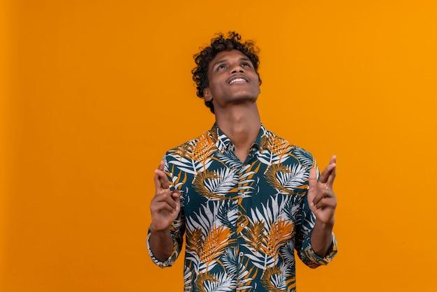 Zadowolony i pozytywny młody przystojny ciemnoskóry mężczyzna z kręconymi włosami w koszulce z nadrukiem w liście, trzymając palce razem, patrząc w górę na pomarańczowym tle