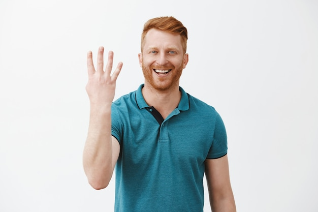 Zadowolony i zadowolony klient rudy mężczyzna z włosiem w zielonej koszulce polo pokazujący numer cztery z palcami i szeroko uśmiechnięty