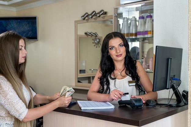 Zadowolony klient dający dolary recepcjonistce w salonie
