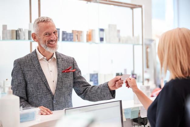 Zadowolony klient płci męskiej uśmiecha się, biorąc plastikową kartę podarowaną mu przez sprzedawcę