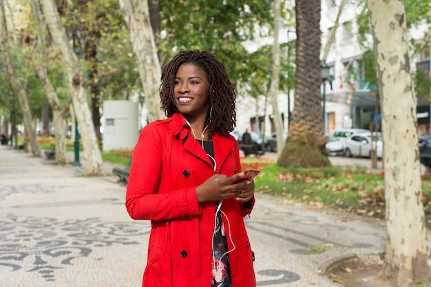 Zadowolony kobiety mienia smartphone i odprowadzenie na ulicie