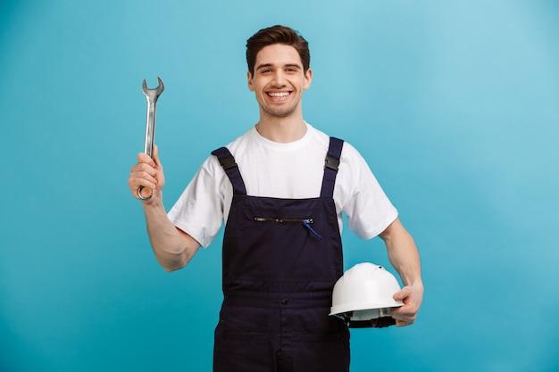 Zadowolony konstruktor trzymający ochronny hełm i klucz, podczas gdy nad niebieską ścianą