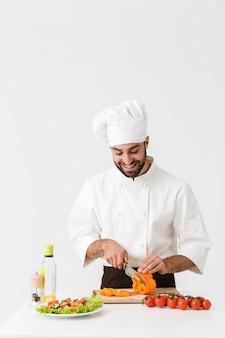 Zadowolony kucharz w mundurze uśmiechający się i krojący sałatkę warzywną na drewnianej desce odizolowanej nad białą ścianą