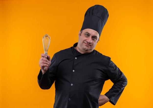 Zadowolony kucharz w średnim wieku w mundurze szefa kuchni trzymający trzepaczkę położył rękę na biodrze na żółtej ścianie