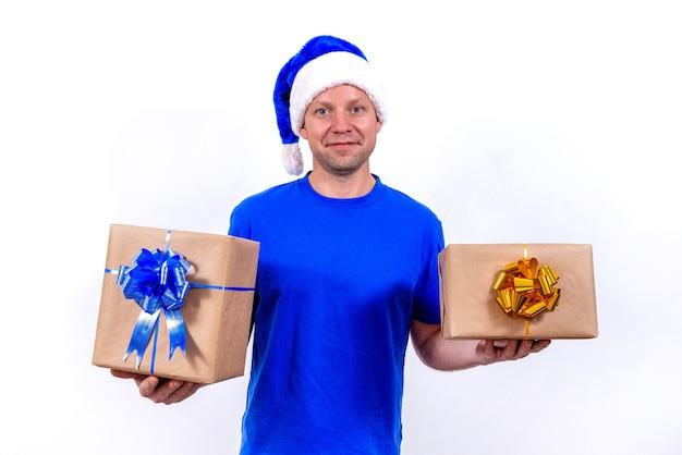 Zadowolony kurier w niebieskim mundurze i czapce mikołaja trzyma dwa pudełka z kokardkami