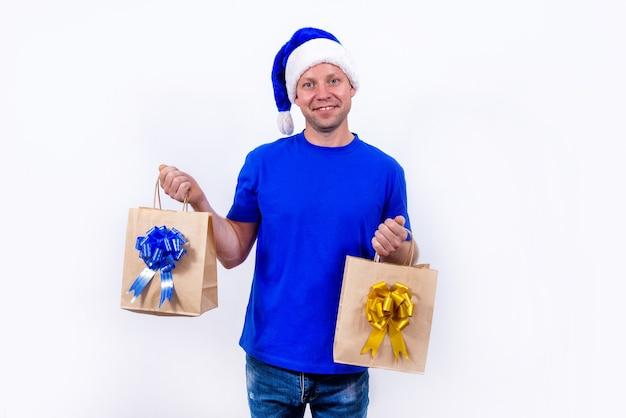 Zadowolony kurier w niebieskim mundurze i czapce mikołaja trzyma dwie torby na prezenty