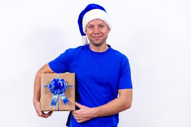 Zadowolony kurier w niebieskim mundurze i czapce mikołaja trzyma pudełko z kokardą