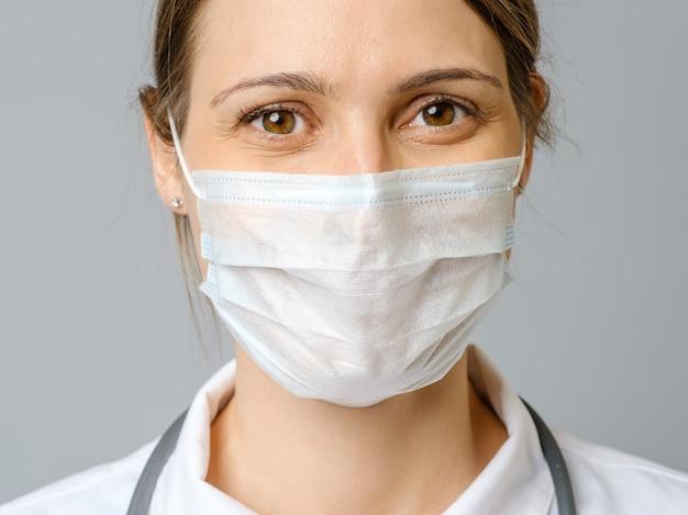 Zadowolony lekarz noszący maskę chirurgiczną z przekonaniem, że przyszłość rozwiąże kryzys. odosobniony