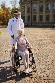 Zadowolony lekarz poruszający się na wózku z emerytem, trzymający kij