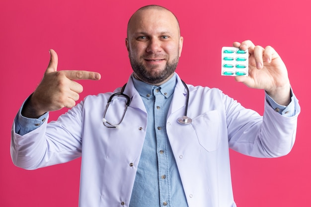 Zadowolony lekarz w średnim wieku ubrany w szatę medyczną i stetoskop pokazujący opakowanie kapsułek medycznych do kamery wskazującej na to izolowane na różowej ścianie