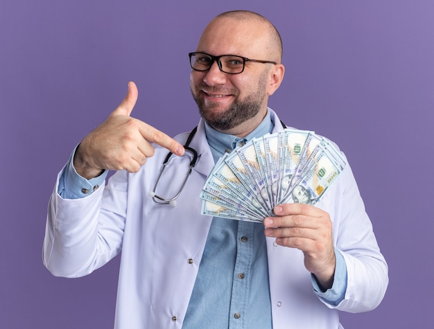 Zadowolony lekarz w średnim wieku ubrany w szatę medyczną i stetoskop w okularach trzymający i wskazujący na pieniądze