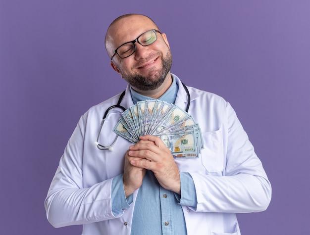 Zadowolony lekarz w średnim wieku ubrany w szatę medyczną i stetoskop w okularach trzymający pieniądze z zamkniętymi oczami odizolowanymi na fioletowej ścianie