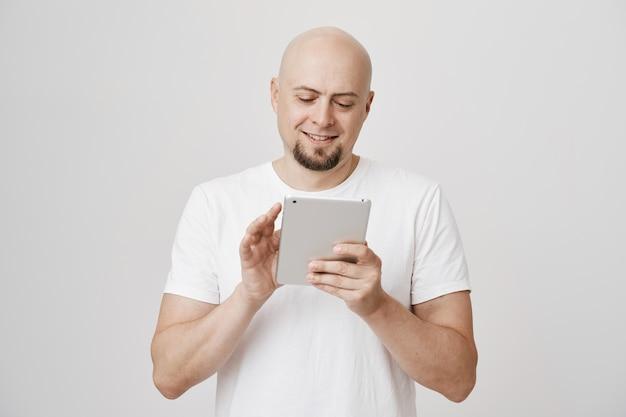 Zadowolony łysy mężczyzna w średnim wieku robi zakupy online za pomocą cyfrowego tabletu