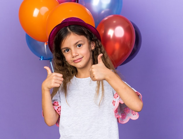 Zadowolony mała dziewczynka kaukaski z fioletowym kapeluszem strony kciuki stojąc przed balonami z helem na białym tle na fioletowej ścianie z miejsca na kopię