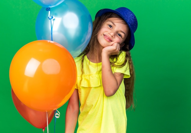 Zadowolony mała dziewczynka kaukaski z niebieską czapką, kładąc rękę na twarzy i trzymając balony z helem na białym tle na zielonej ścianie z miejsca na kopię
