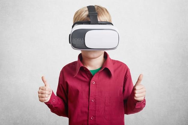 Zadowolony mały chłopiec lubi wirtualną rzeczywistość, nosi słuchawki vr lub okulary 3d, pokazuje znak ok, jako zadowolony z efektu, gra w gry online na białym tle. innowacyjna technologia