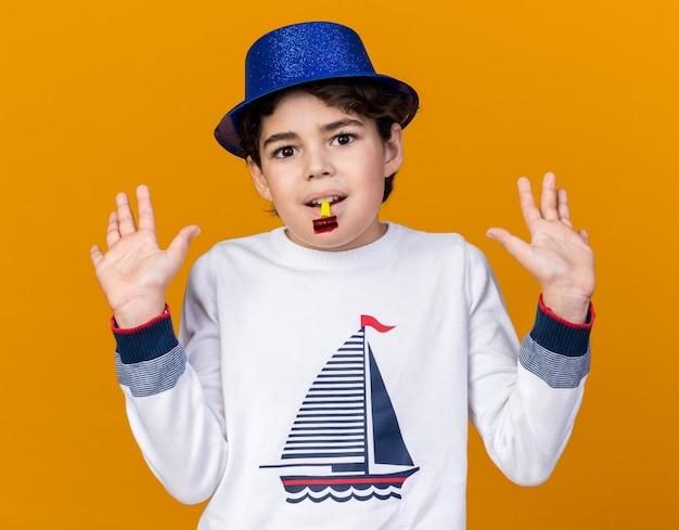 Zadowolony mały chłopiec ubrany w niebieską imprezową czapkę, dmuchający gwizdek, rozkładający ręce