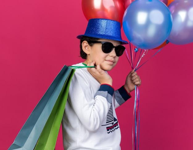 Zadowolony mały chłopiec w niebieskiej imprezowej czapce w okularach, trzymający balony i torby na prezenty