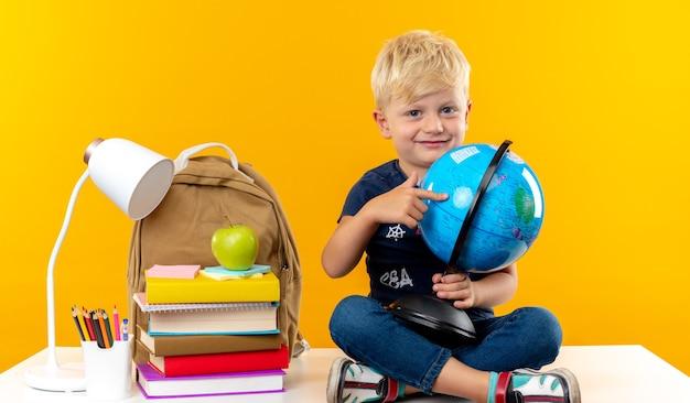 Zadowolony mały chłopiec w szkole siedzący na stole z narzędziami szkolnymi trzymającymi i wskazującymi na kulę ziemską