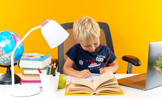 Zadowolony mały chłopiec w szkole siedzi przy stole z szkolnymi narzędziami, pisząc coś na zeszycie