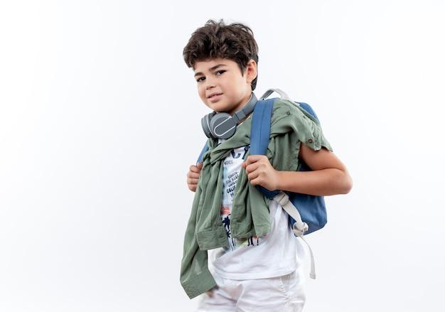Zadowolony mały uczeń na sobie tylną torbę i słuchawki na białym tle