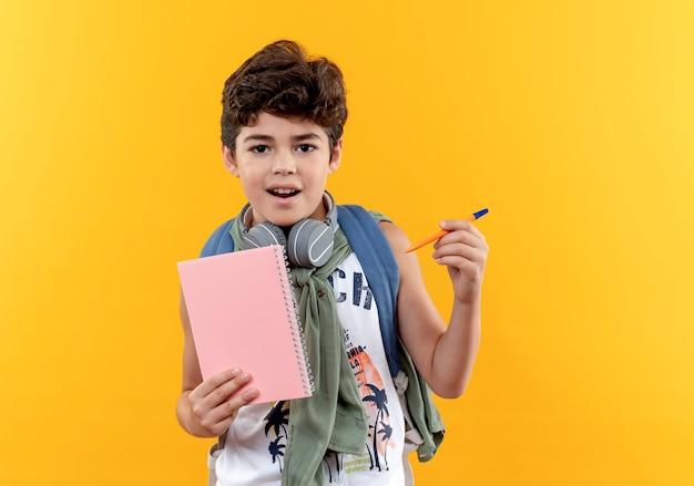 Zadowolony mały uczeń noszący torbę na plecach i słuchawki trzymający notatnik z długopisem