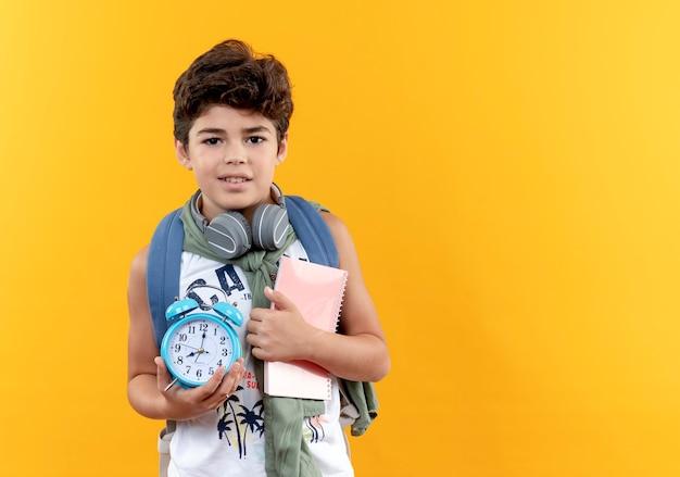 Zadowolony mały uczeń noszenia plecaka i słuchawek, trzymając książkę z budzikiem na białym tle na żółtym tle z miejsca na kopię