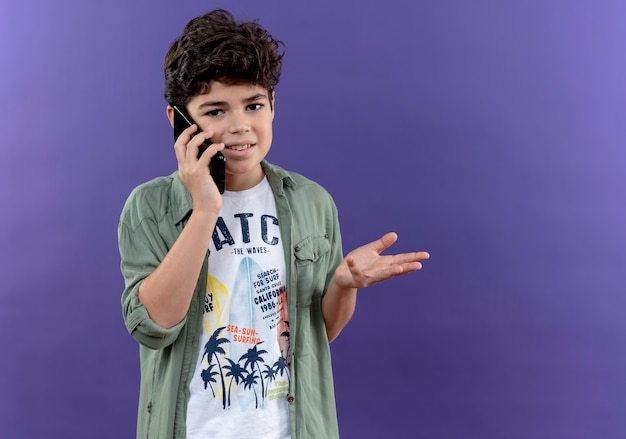 Zadowolony mały uczeń rozmawia przez telefon i rozkłada dłoń