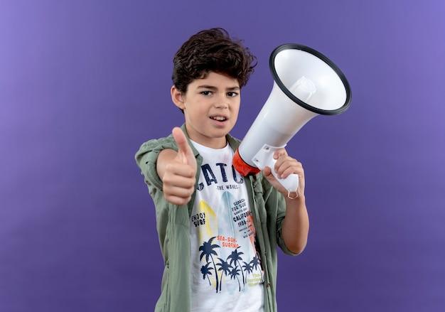 Zadowolony mały uczeń trzymając głośnik kciuk w górę na białym tle na fioletowej ścianie
