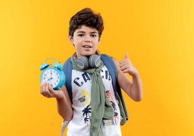 Zadowolony mały uczeń ubrany w torbę i słuchawki, trzymając budzik kciuk w górę