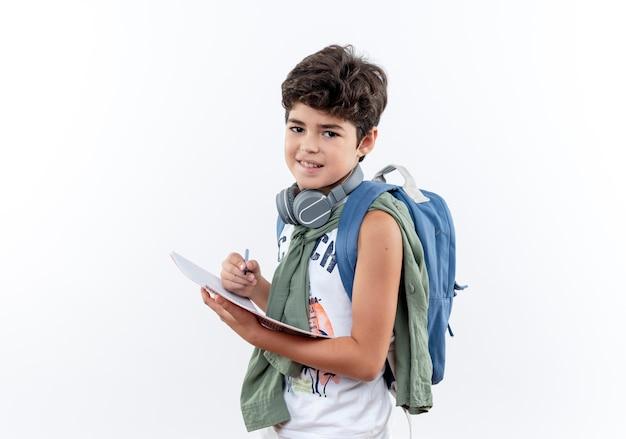 Zadowolony mały uczeń ubrany z powrotem torbę i słuchawki trzymając notebook z piórem na białym tle na białym tle z miejsca na kopię