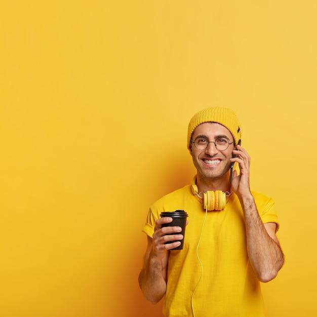 Zadowolony męski model dzwoni do przyjaciela przez telefon komórkowy, trzyma telefon komórkowy, lubi rozmowę podczas picia kawy na wynos, nosi żółte ubrania, przezroczyste okulary