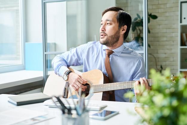 Zadowolony mężczyzna gra na gitarze w pracy