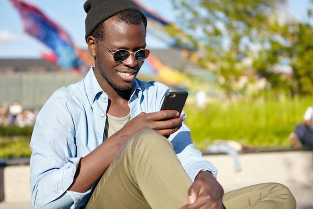 Zadowolony mężczyzna o ciemnej skórze, noszący okulary przeciwsłoneczne i modne ciuchy, czytający przyjemne sms na telefonie komórkowym, wpisujący odpowiedź. uśmiechnięty ciemnoskóry mężczyzna korzystający ze smartfona na zewnątrz, będąc zawsze w kontakcie