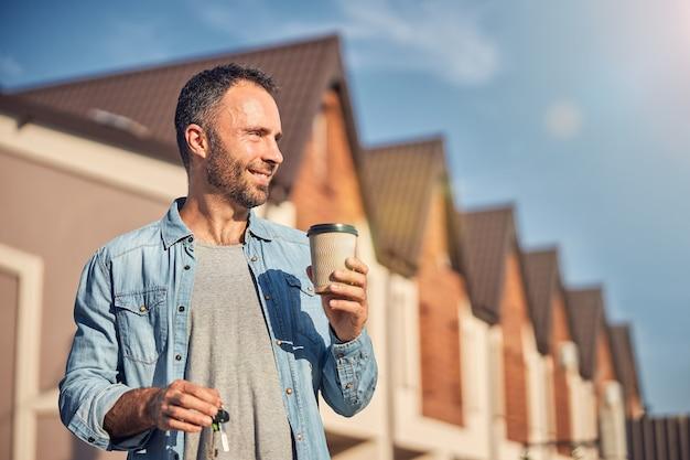 Zadowolony mężczyzna pijący poranną kawę w pobliżu swojego nowego domu