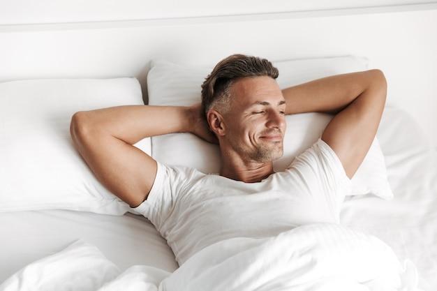 Zadowolony mężczyzna relaksujący się w łóżku