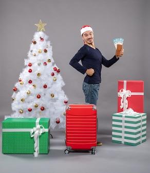 Zadowolony mężczyzna stoi z boku, trzymając swoje bilety podróżne i pokazując mięśnie ramion z niecierpliwością
