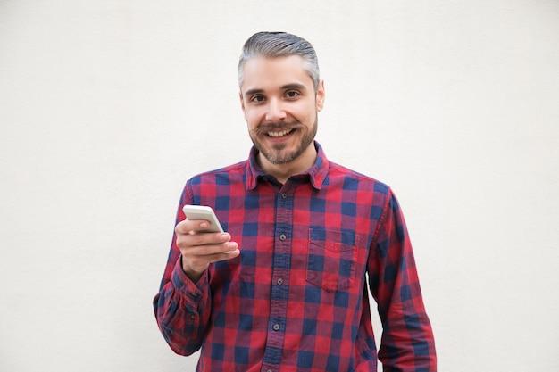 Zadowolony mężczyzna trzyma smartphone i ono uśmiecha się