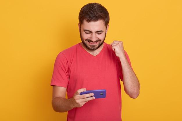 Zadowolony mężczyzna ubiera czerwoną przypadkową koszulkę, grając w grę wideo na telefon komórkowy i zaciskając pięść na białym tle nad żółtym studio
