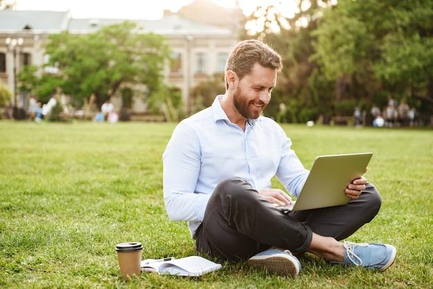 Zadowolony mężczyzna w biznesowym ubraniu, siedzący na trawie w parku ze skrzyżowanymi nogami i pracujący na srebrnym laptopie