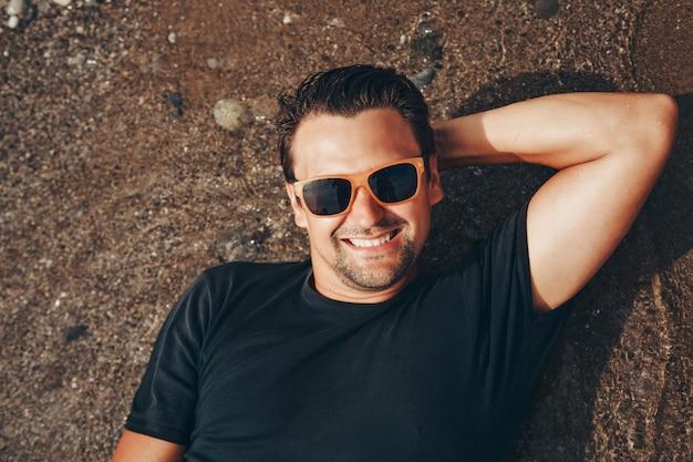Zadowolony mężczyzna w okularach przeciwsłonecznych z rękami za głową nad wodą. wakacje nad morzem